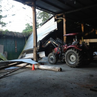 The roof had caved in on the side part of the barn.  Ronnie got the tractor and tried to lift and clear the debris.