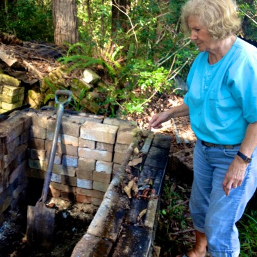 Shirley Featherstone examining the state of the kiln prior to loading it.  The remains of the past firing had to be shovelled out.