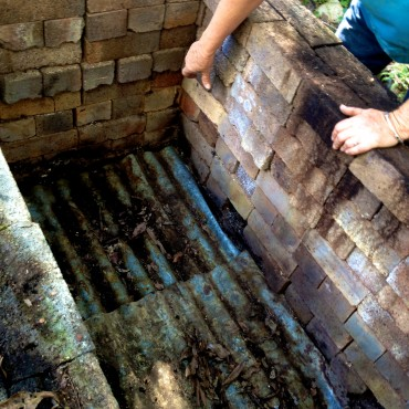 Sheets of old corrugated tin were laid over the bricks on the bottom of the pit fire kiln.