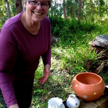 Ronda Luland loading her pots into the pit.