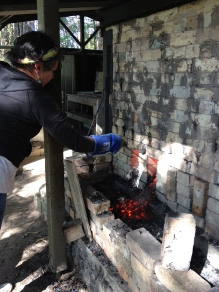 Julie tending the side of the kiln and the coals.