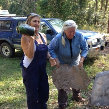 Carole and Ann wrapping the clay around the chook.
