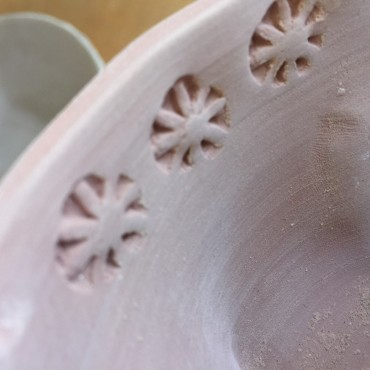Stamped rim of blow with handmade clay stamp.
