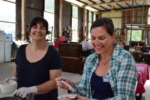 Kirsten and Maria glazing pots.