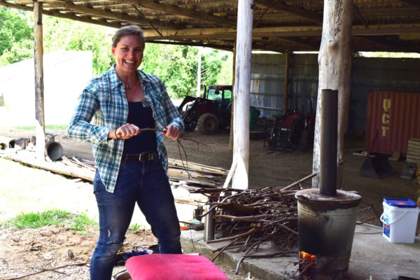 Maria preparing wood for the wood-fired raku kiln.